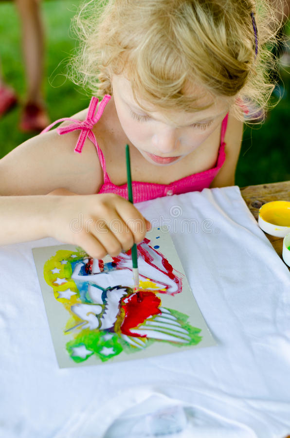 Child painting. Beautiful blond girl painting with brush into t-shirt with colorful colors royalty free stock photos