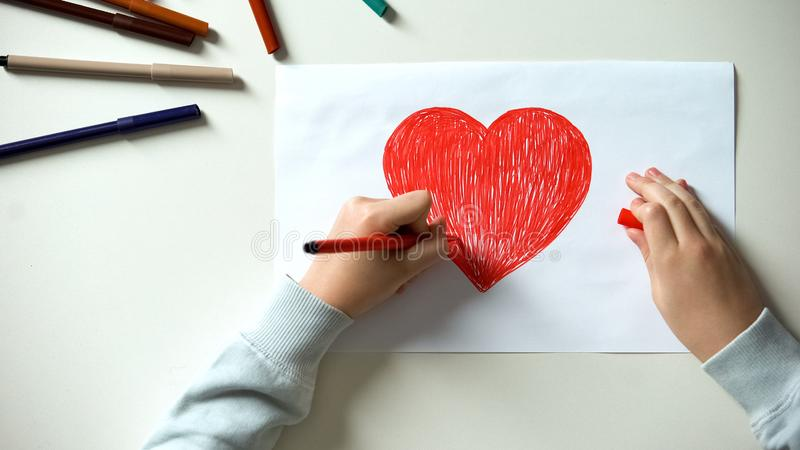 Child painting big red heart, Saint Valentines Day gift, first love, childhood royalty free stock image