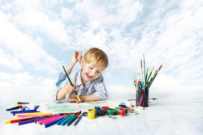 Child painting with color brush, drawing tools, creative kid. Child painting with color brush using a lot of drawing tools. Happy creative kid artist over blue stock photo