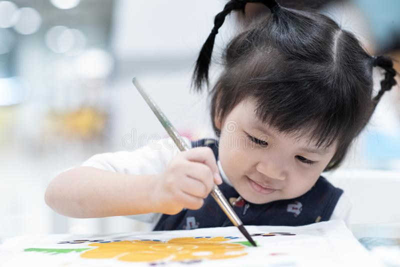 Child painting color using brush on paper. enjoy, smile, happy, clever and dream royalty free stock photo