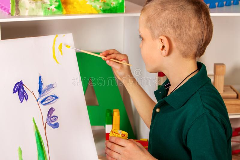 Child painting finger on easel. Kid boy learn paint school. stock images