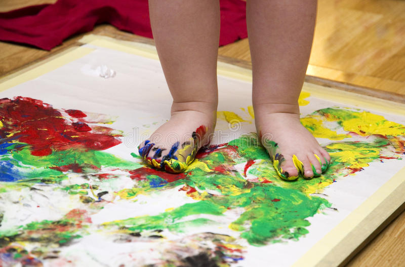 Child painting by feet. On a white paper. Detail of legs royalty free stock images