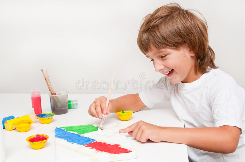 Child painting. Happy child boy painting with colors stock image