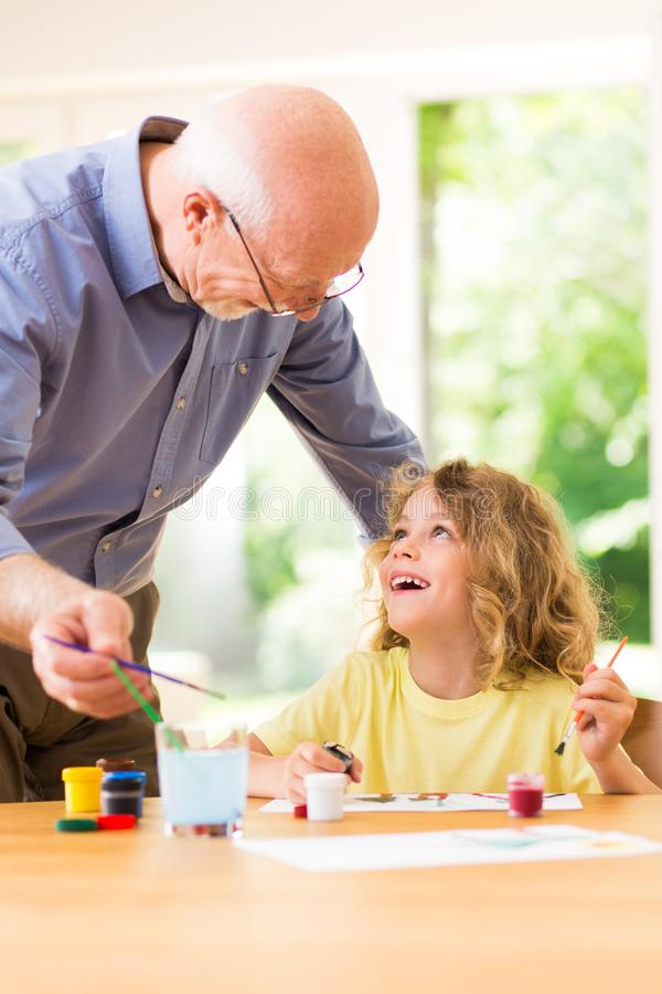 Child painting with his grandfather, spending time together stock photos