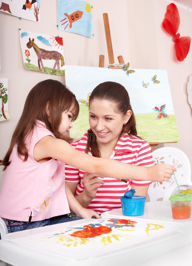 Child painting with mother at home. stock image