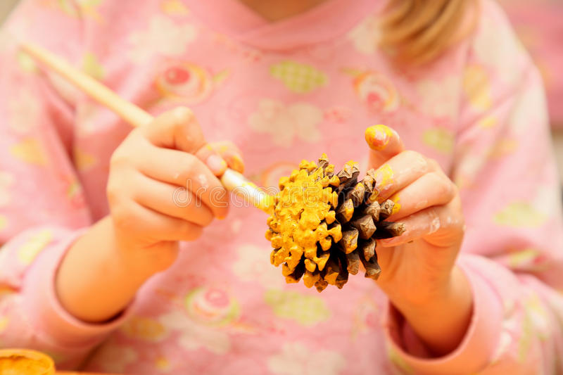 The child painting pinecone stock image