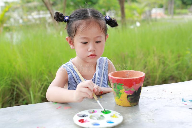Child painting, Portrait little girl having fun to paint on earthenware dish.  stock photography