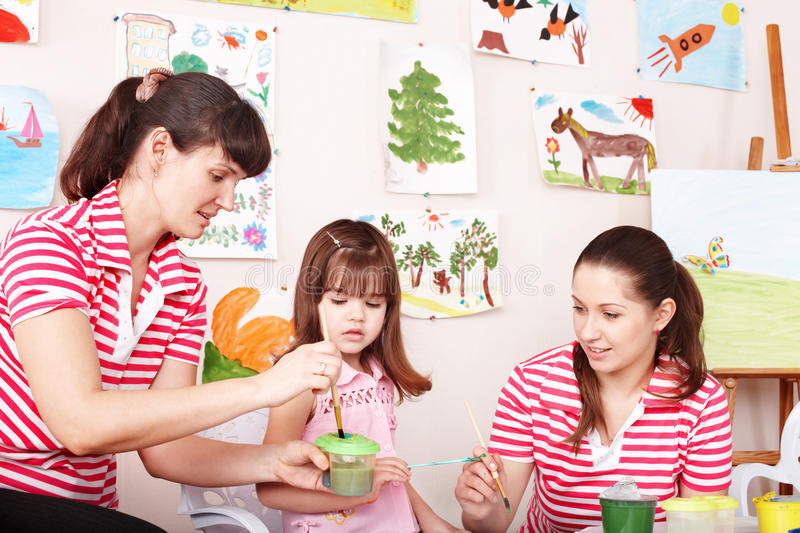 Child painting with teacher in preschool. Little girl painting with teacher in preschool stock photo