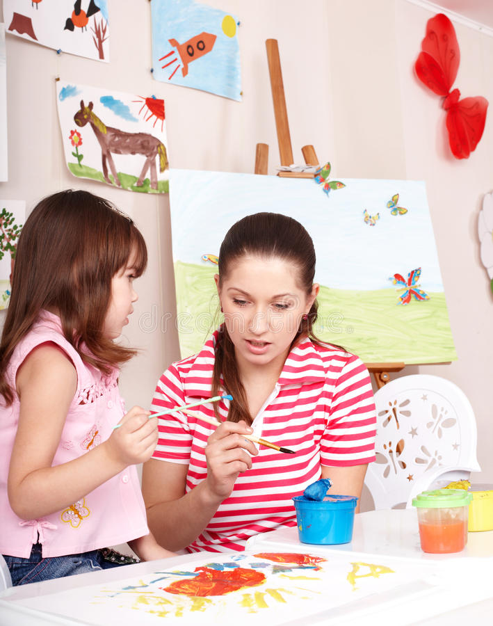 Child painting with teacher in preschool. Little girl painting with teacher in preschool royalty free stock photography