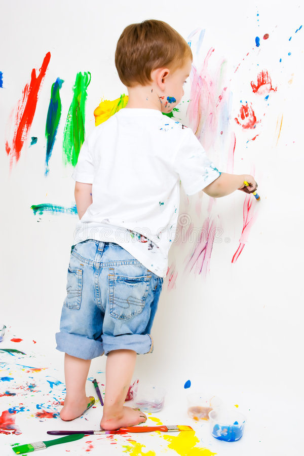 Child painting on the wall and floor stock photography