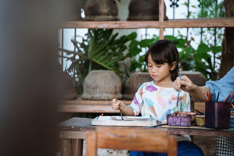 Child painting on white fabric stock photo