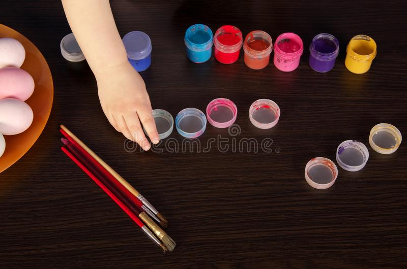 A child paints Easter eggs. hand, paintbrush and paint on the table. preparation for Easter stock photos