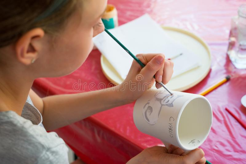 Child paints a mug in a pottery workshop royalty free stock image
