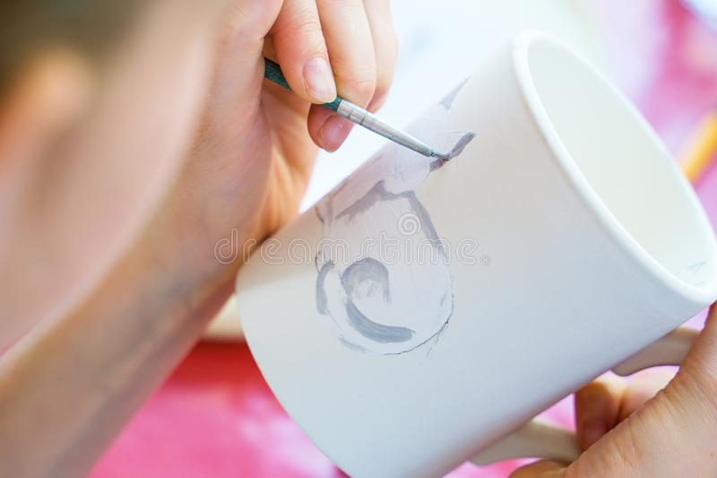 Child paints a mug in a pottery workshop stock images