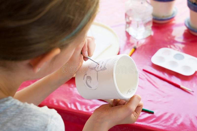 Child paints a mug in a pottery workshop stock photos