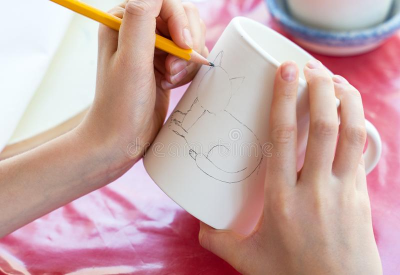 Child paints a mug in a pottery workshop royalty free stock photos