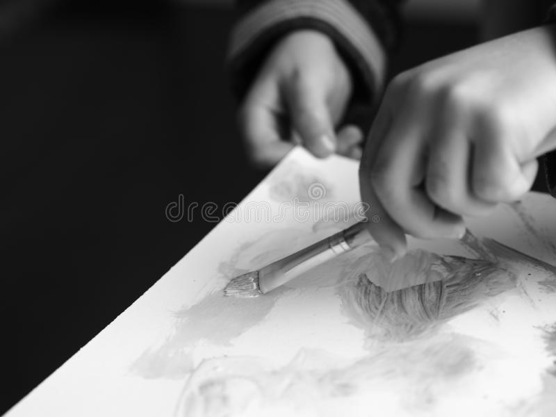 A child paints a picture with a brush and watercolor, blackandwhite picture stock images