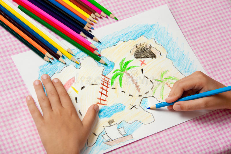 Child paints a picture of pencils pirate treasure map. royalty free stock photos