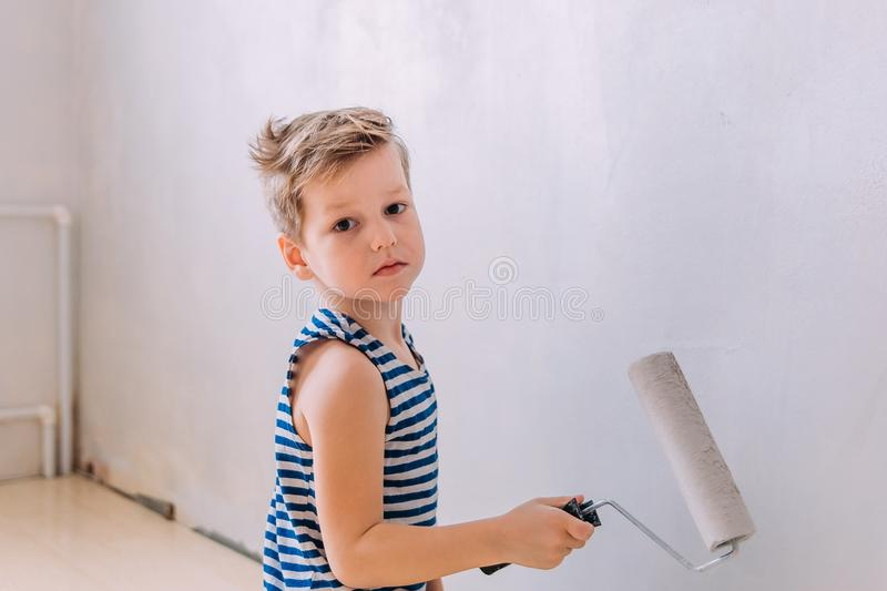 Five-year-old boy paints the wall with white paint. The child paints the wall,mother`s helper, child labor, new flat, repair royalty free stock images