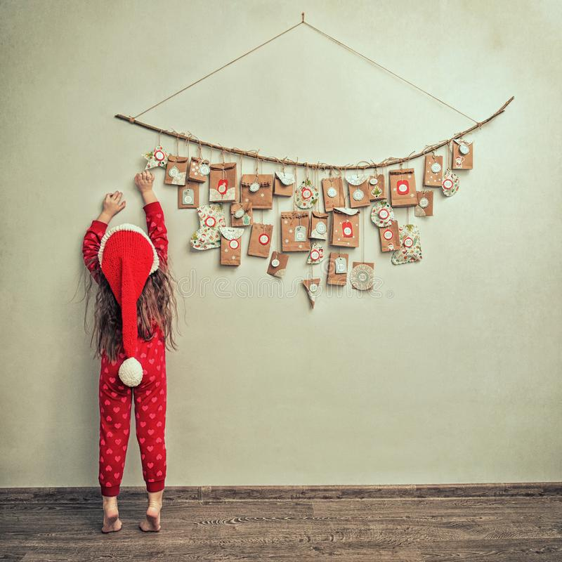 Child in pajamas and Christmas cap stretches for advent calendar with small gifts. kid counts days until new year royalty free stock images