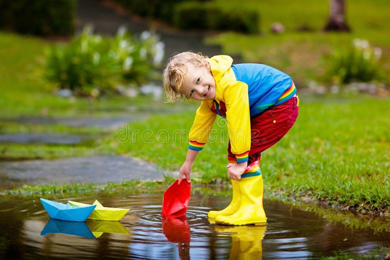 Child with paper boat in puddle. Kids by rain. stock image