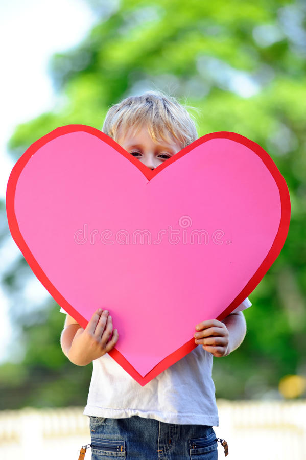 Child with paper heart. Young child holds a big pink paper heart stock photography