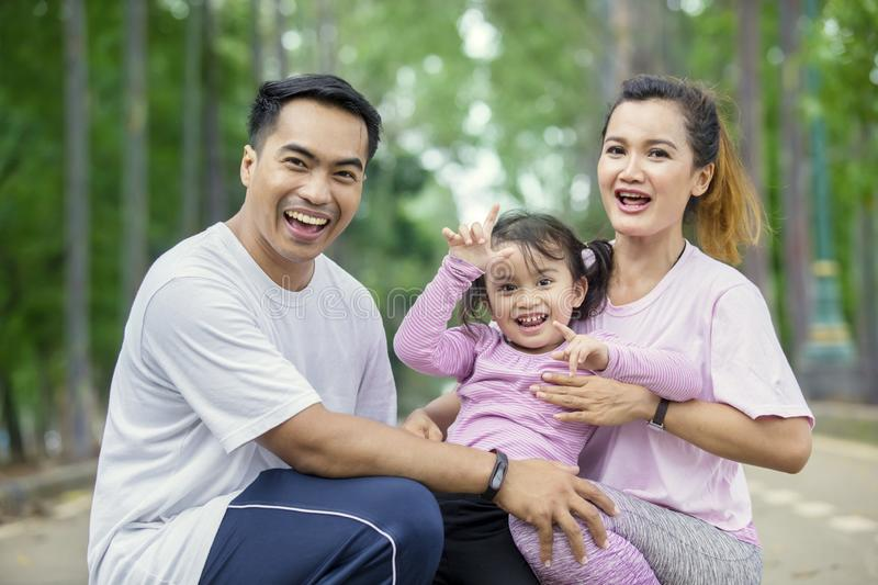 Child and parents smiling at the camera stock photo