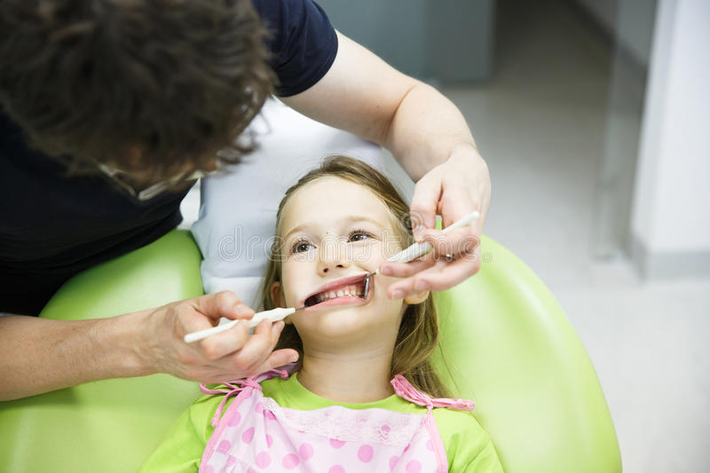 Child patient on her regular dental checkup. Little girl in paediatric dentists office on her regular checkup for tooth decay, caries and gum disease. Early royalty free stock images