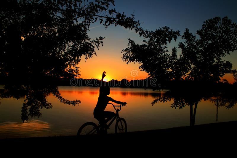 Child pedaling bicycle at the dusk of the lagoon stock photography