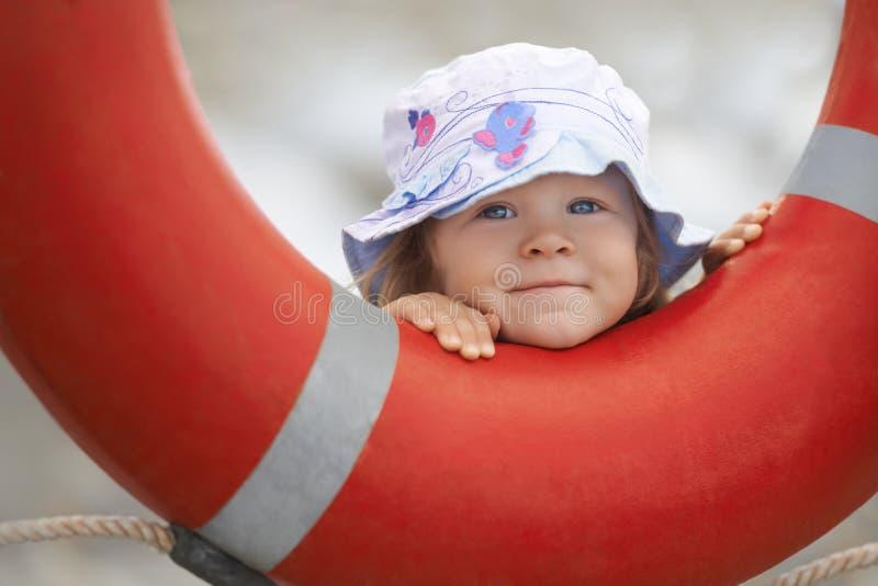 Child peeking out of the lifebuoy stock photos