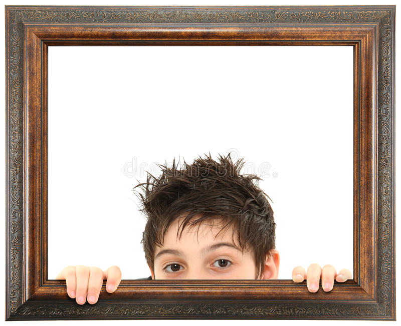 Child Peeking Out of Ornate Wooden Frame. Attractive 8 year old boy peeking out of ornate stained wooden frame over white isolation royalty free stock image