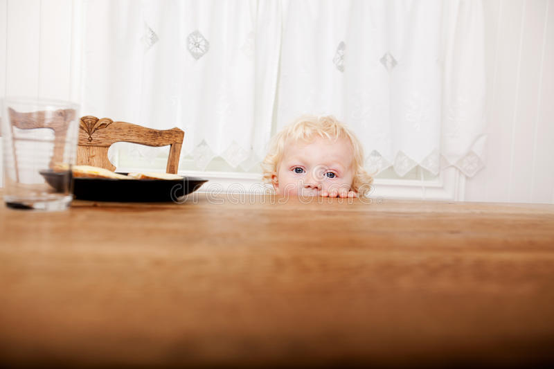 Child Peeking Over Table. A young toddler peeking over the edge of the table before meal time royalty free stock photos