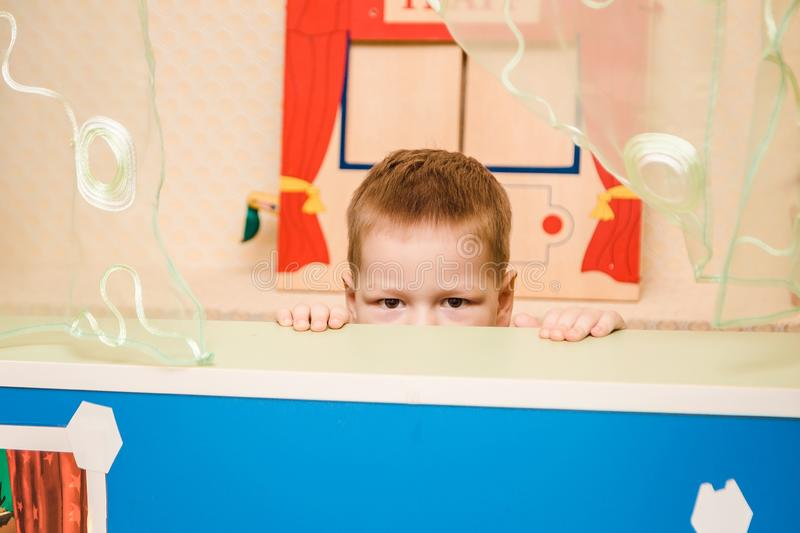A child peeks out from behind a house in kindergarten stock photography