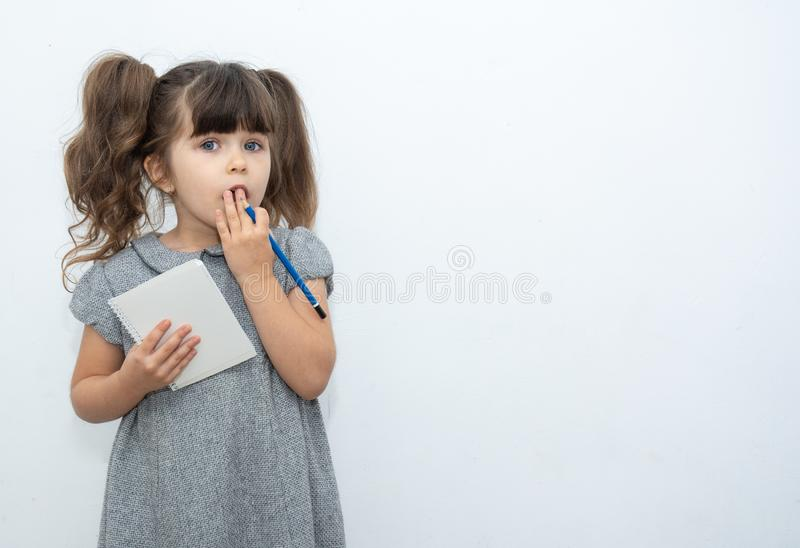 Child with pen and blank paper book on empty banner on which you can write any text. Crazy expression. Child with pen and blank paper book on empty banner on stock images