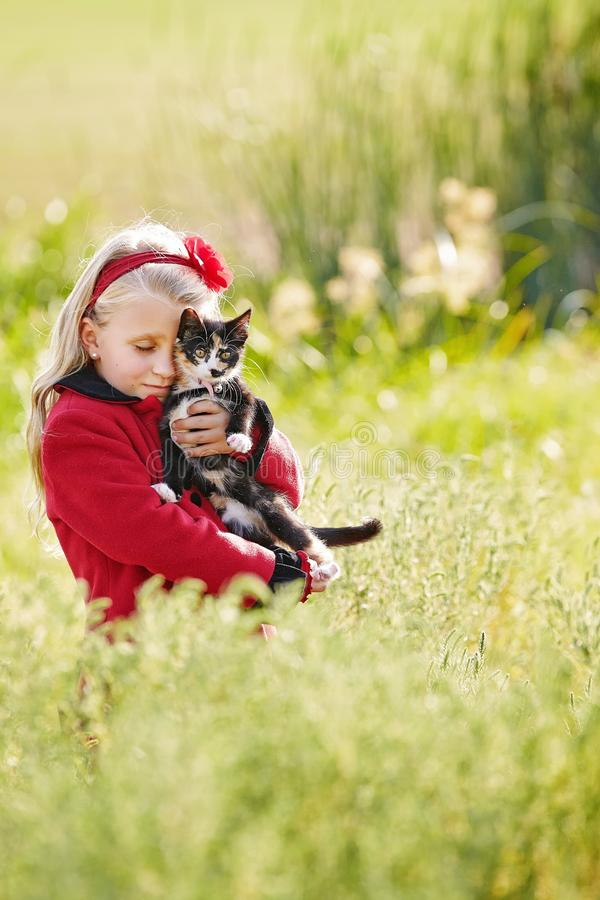 Child and pet. A cute little Caucasian girl, dressed in red, embracing her little black and white kitten in green pasture outdoors royalty free stock photos