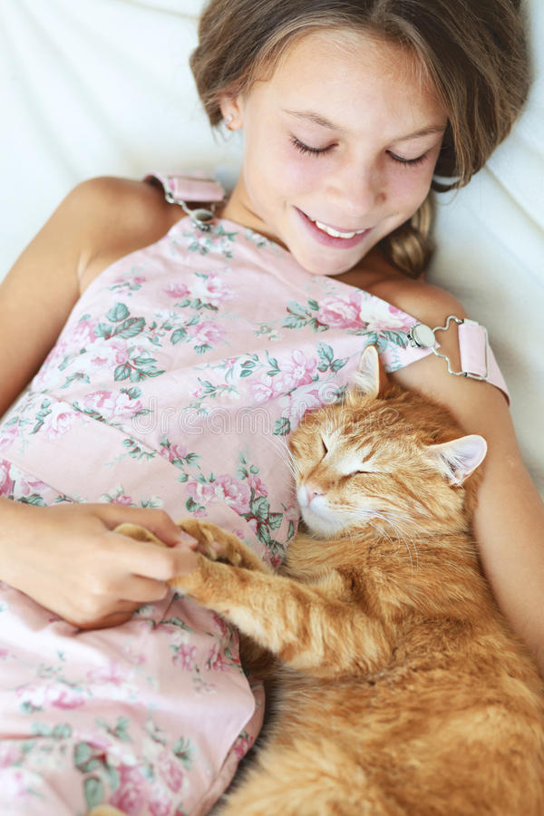 Child and a pet. Preteen school girl of 8-9 years old with her pet resting on a sofa at home royalty free stock photography