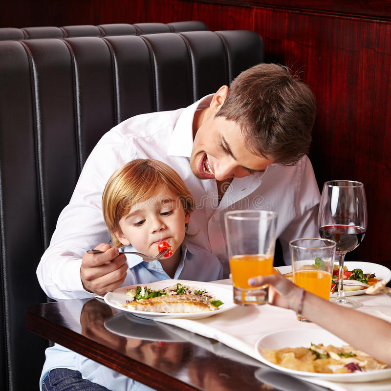 Child is picky eater in restaurant. Child is a picky eater in restaurant and father tries to feed it stock images