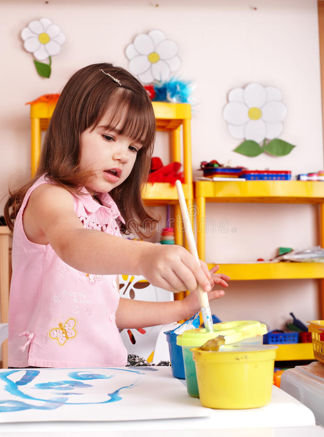 Child with picture and brush in play room. Preschool royalty free stock photos