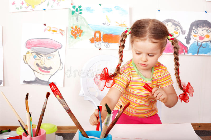 Child with picture and brush in playroom. royalty free stock photos
