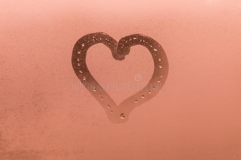 The child picture or figure of the heart on the orange or pink evening or morning window glass stock image