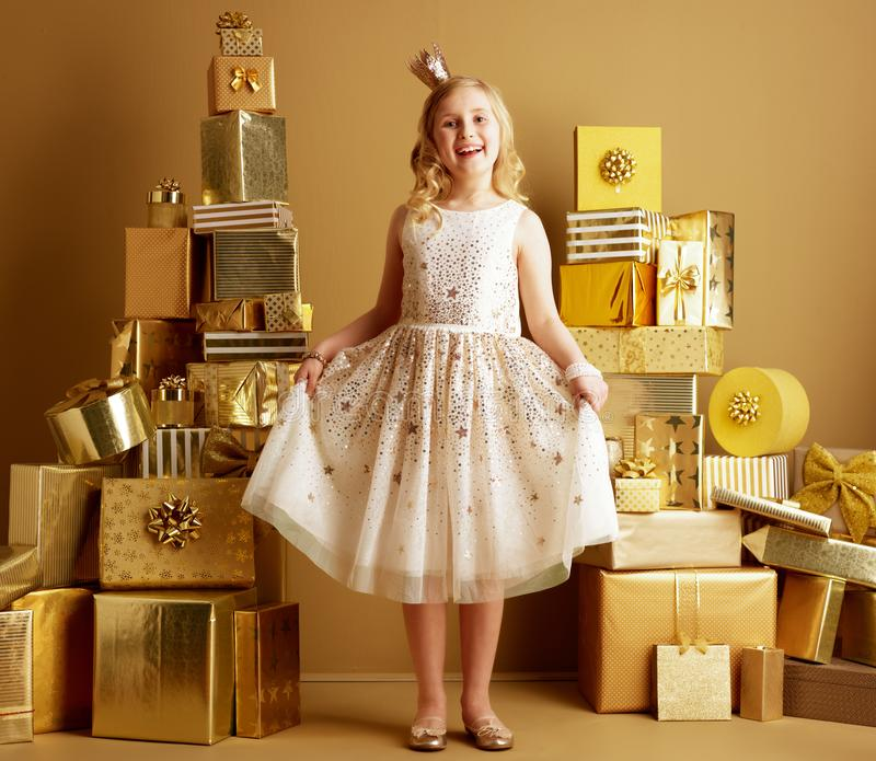 Child among 2 piles of golden gifts in front of plain wall stock photography