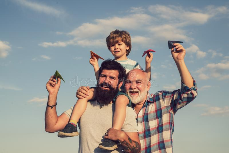 Child pilot aviator with paper airplane dreams of traveling. Dream of flying. Cute son with dad playing outdoor. Father. And son playing on blue summer sky royalty free stock photo
