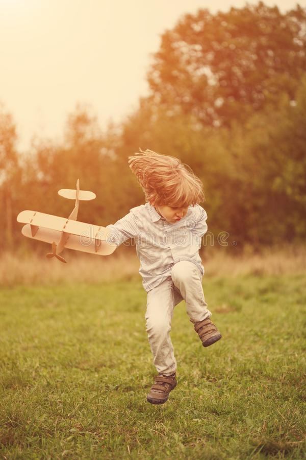 Child pilot aviator with plane at sunset, little boy playing with cardboard toy airplane outdoors, against summer sky background. stock photography