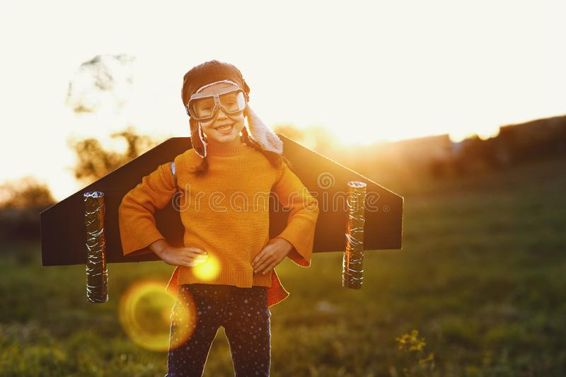 Child pilot aviator with wings of airplane dreams of traveling in summer  at sunset stock images
