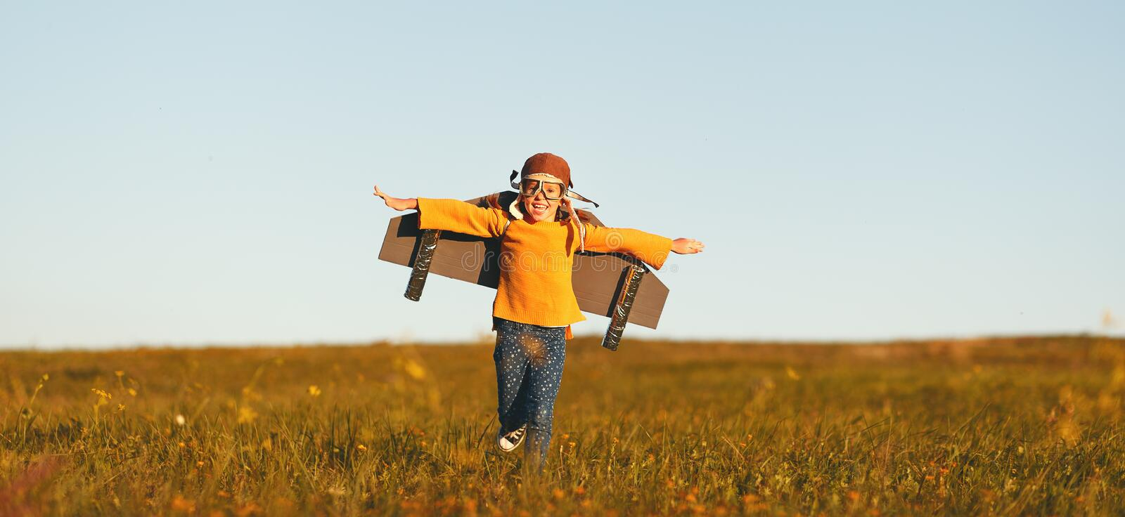 Child pilot aviator with wings of airplane dreams of traveling in summer  at sunset. Child pilot aviator with wings of airplane dreams of traveling in summer in royalty free stock photo
