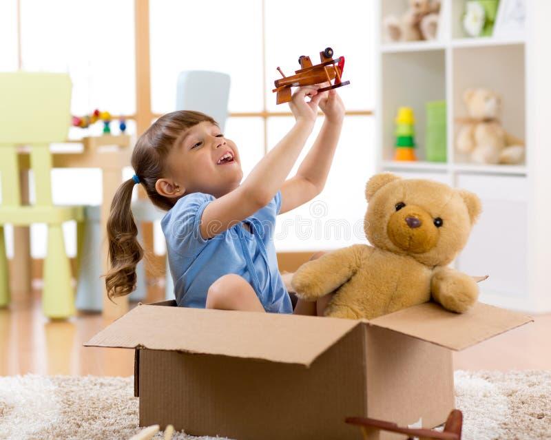Child pilot flying a cardboard box. Kid girl pilot flying a cardboard box in children room royalty free stock photo