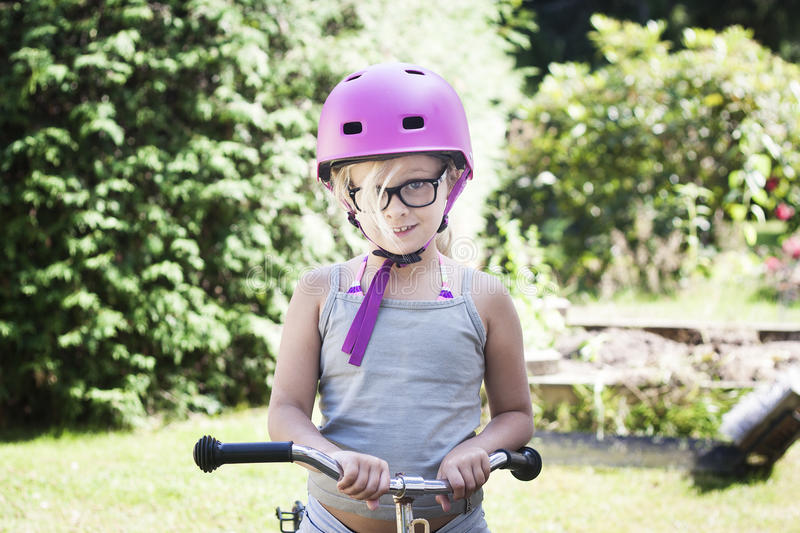 Child with pink bicycle helmet and black glasses on bike. 7 year old girl with bicycle with bike helmet and specs royalty free stock image