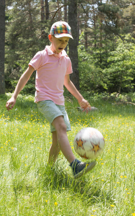 Child play with a ball in the mountain. Green grass royalty free stock photos