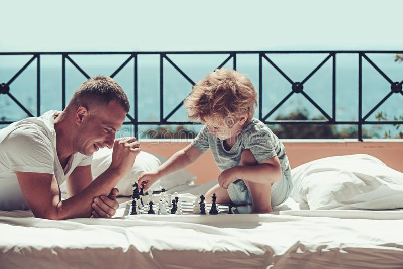 Child play chess with father. Summer vacation of happy family. Family travel with kid on fathers day. father with son on royalty free stock images