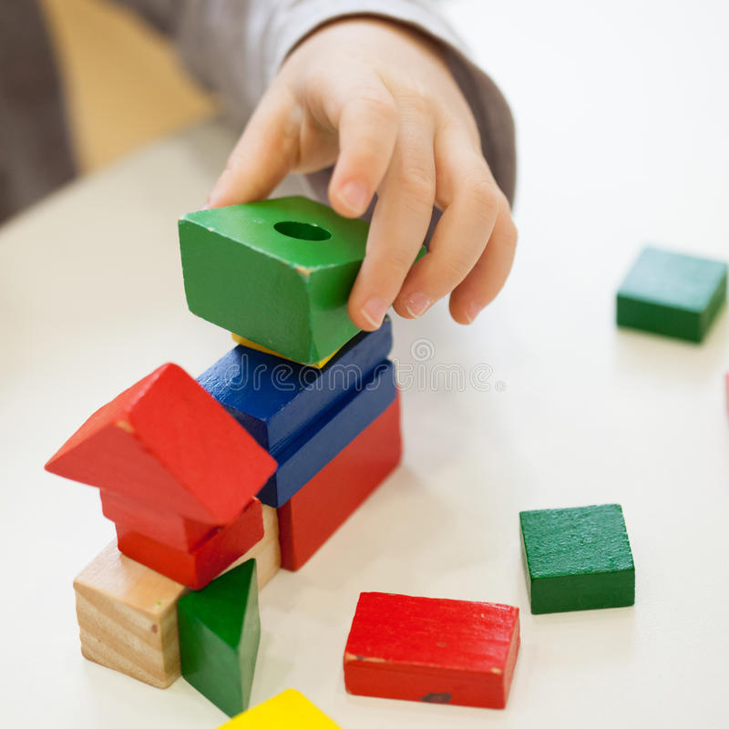 Child play with colored wooden brick shapes. On white table. Close up view from above on hands and toys royalty free stock images